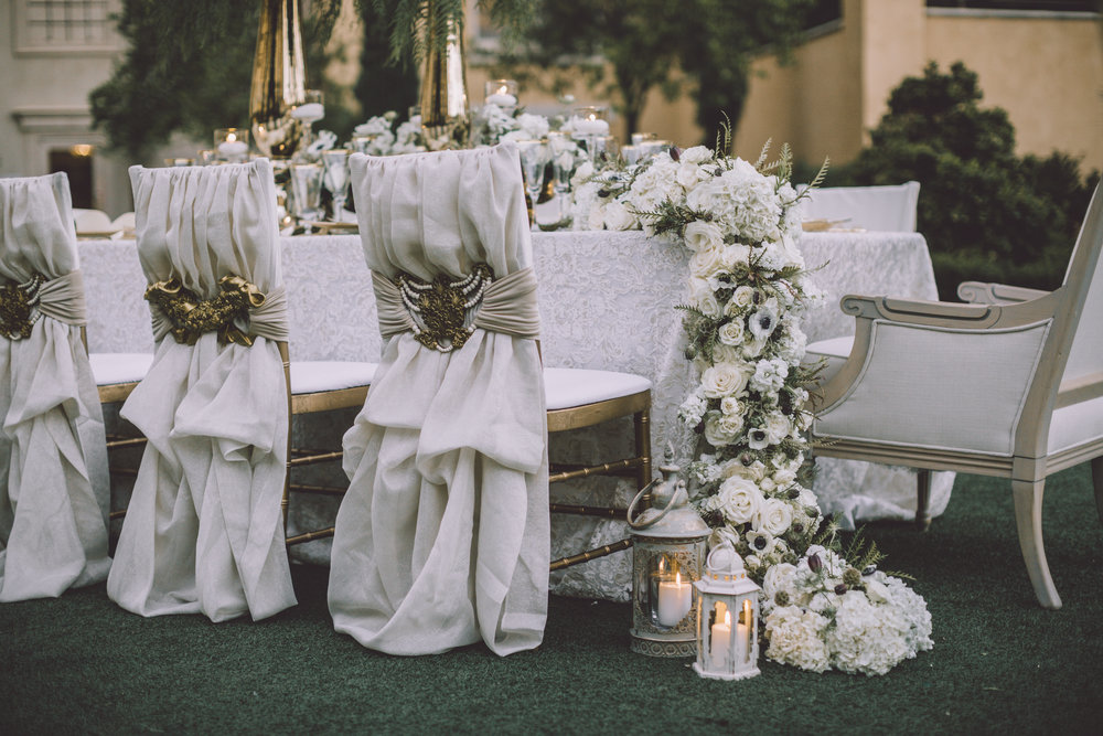 Upscale, expensive wedding details like custom chairs, tables with thick floral runners, and lanterns add texture and interest to a long wedding banquet table.  Photo by Adam Trujillo.