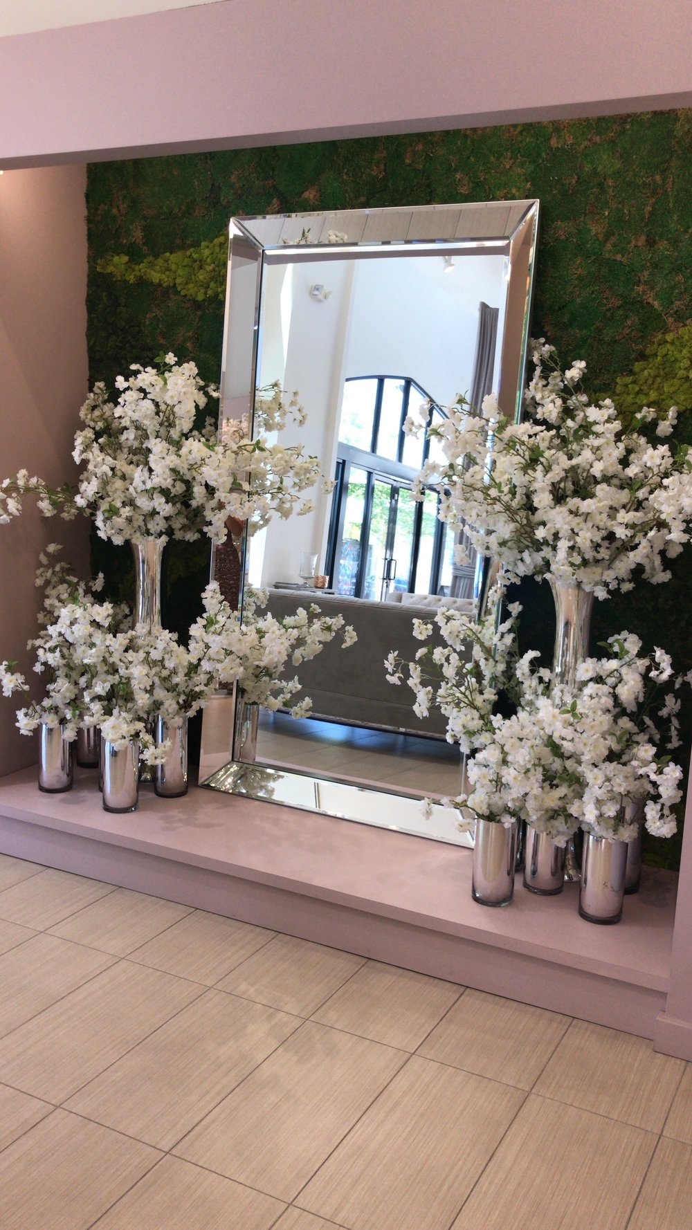 Large mirror against a hedge all with white floral accents.
