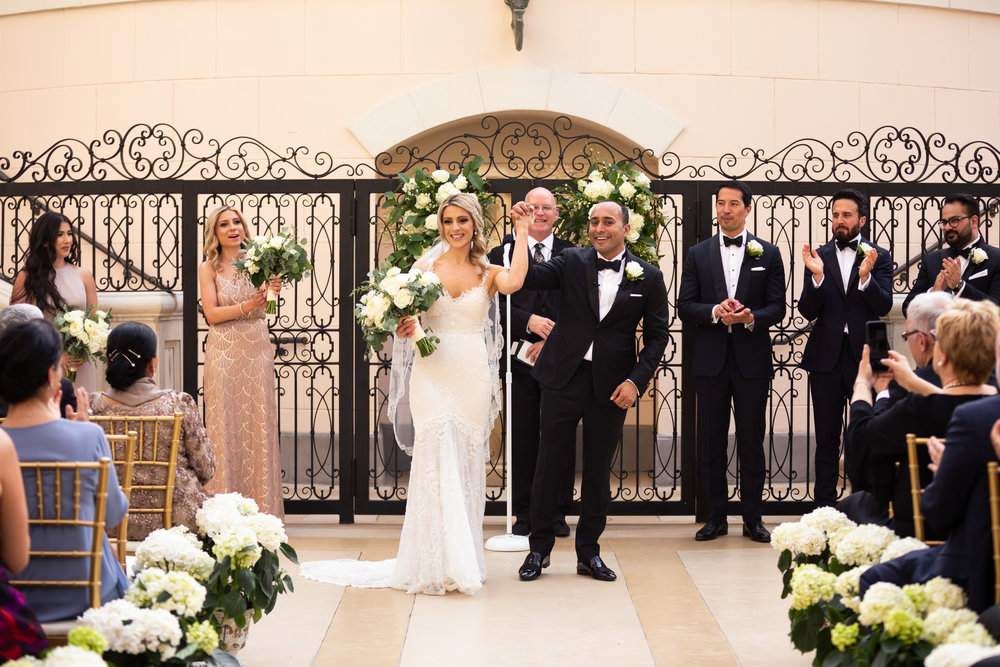 Bride and Groom in front of the gates at The Bellagio.  Wedding Planner:  Andrea Eppolito Events   |   Photography  D2 Tuscan Wedding Photography   |  Videography  M Place Productions   |  Venue & Catering:  Bellagio   |  Floral & Decor:  Destinations by Design    |  Lighting:  LED Unplugged   |  Music: Classical Entertainment &  DJ Mike Fox   |  Hair & Make Up:  Amelia C & Co
