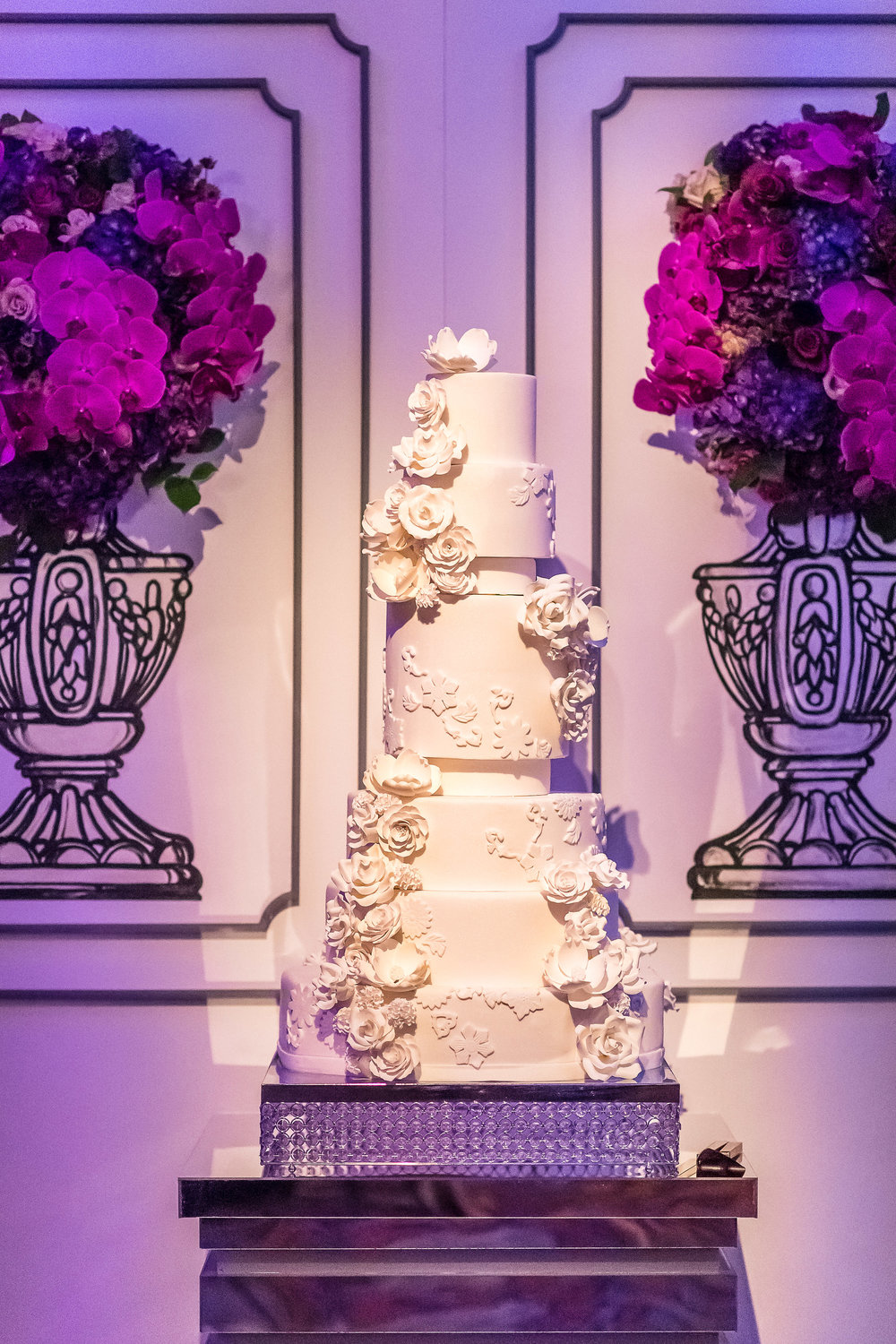 White wedding cake with lace fondant and sugar roses.  Living flower wall.  Wedding Planner:  Andrea Eppolito Events  |   Photography  Brian Leahy   |  Videography  HOO Films   |  Venue & Catering:  Mandarin Oriental  / Waldorf Astoria |  Floral & Decor:  Destinations by Design    |  Lighting:  LED Unplugged  |  Music:  DJ Breeze II   |  Hair & Make Up:  Amelia C & Co   |  Invitations by  Bliss & Bone   |  Menu and Escort Cards by  Meldeen