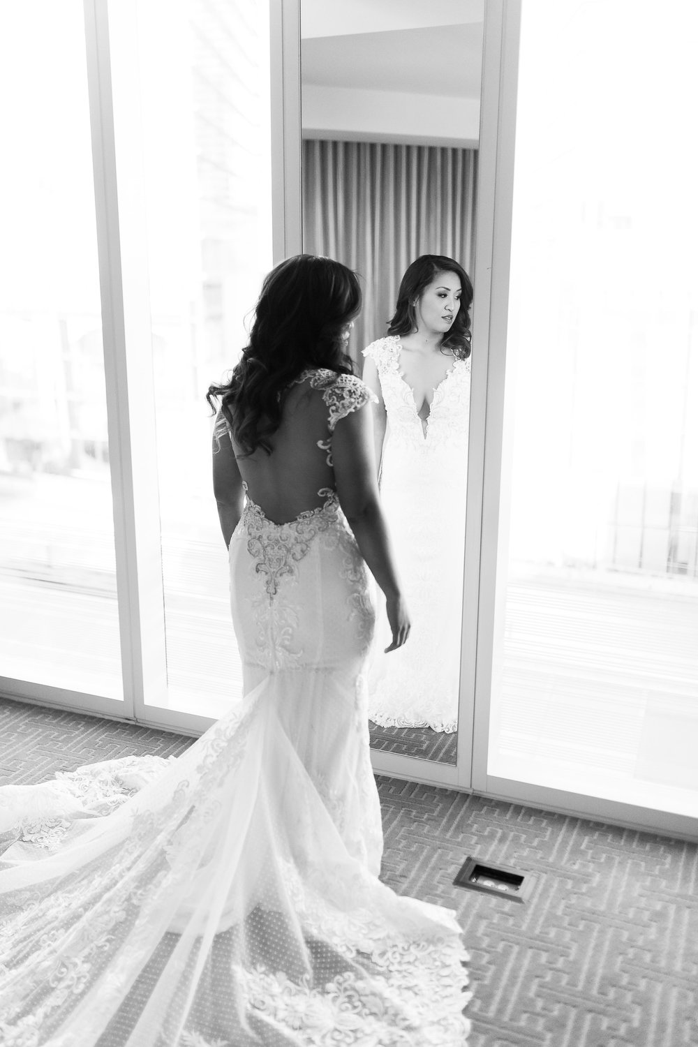 Bride in backless lace wedding dress.  Wedding Planner:  Andrea Eppolito Events  |   Photography  Brian Leahy   |  Videography  HOO Films   |  Venue & Catering:  Mandarin Oriental  / Waldorf Astoria |  Floral & Decor:  Destinations by Design    |  Lighting:  LED Unplugged  |  Music:  DJ Breeze II   |  Hair & Make Up:  Amelia C & Co   |  Invitations by  Bliss & Bone   |  Menu and Escort Cards by  Meldeen