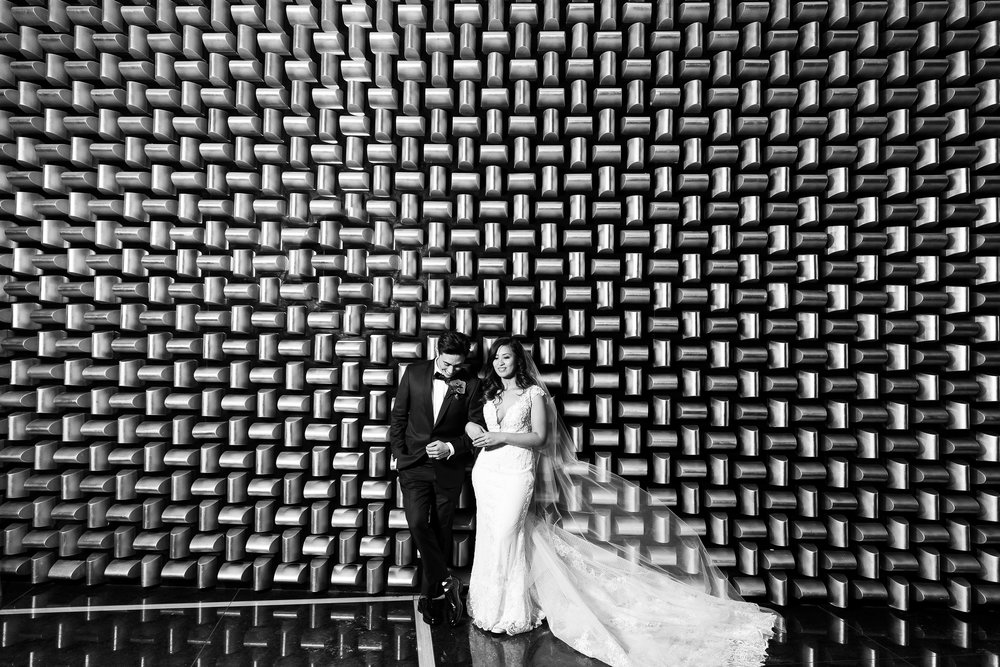 Black and white image of bride and groom at the gold wall.  Wedding Planner:  Andrea Eppolito Events  |   Photography  Brian Leahy   |  Videography  HOO Films   |  Venue & Catering:  Mandarin Oriental  / Waldorf Astoria |  Floral & Decor:  Destinations by Design    |  Lighting:  LED Unplugged  |  Music:  DJ Breeze II   |  Hair & Make Up:  Amelia C & Co   |  Invitations by  Bliss & Bone   |  Menu and Escort Cards by  Meldeen