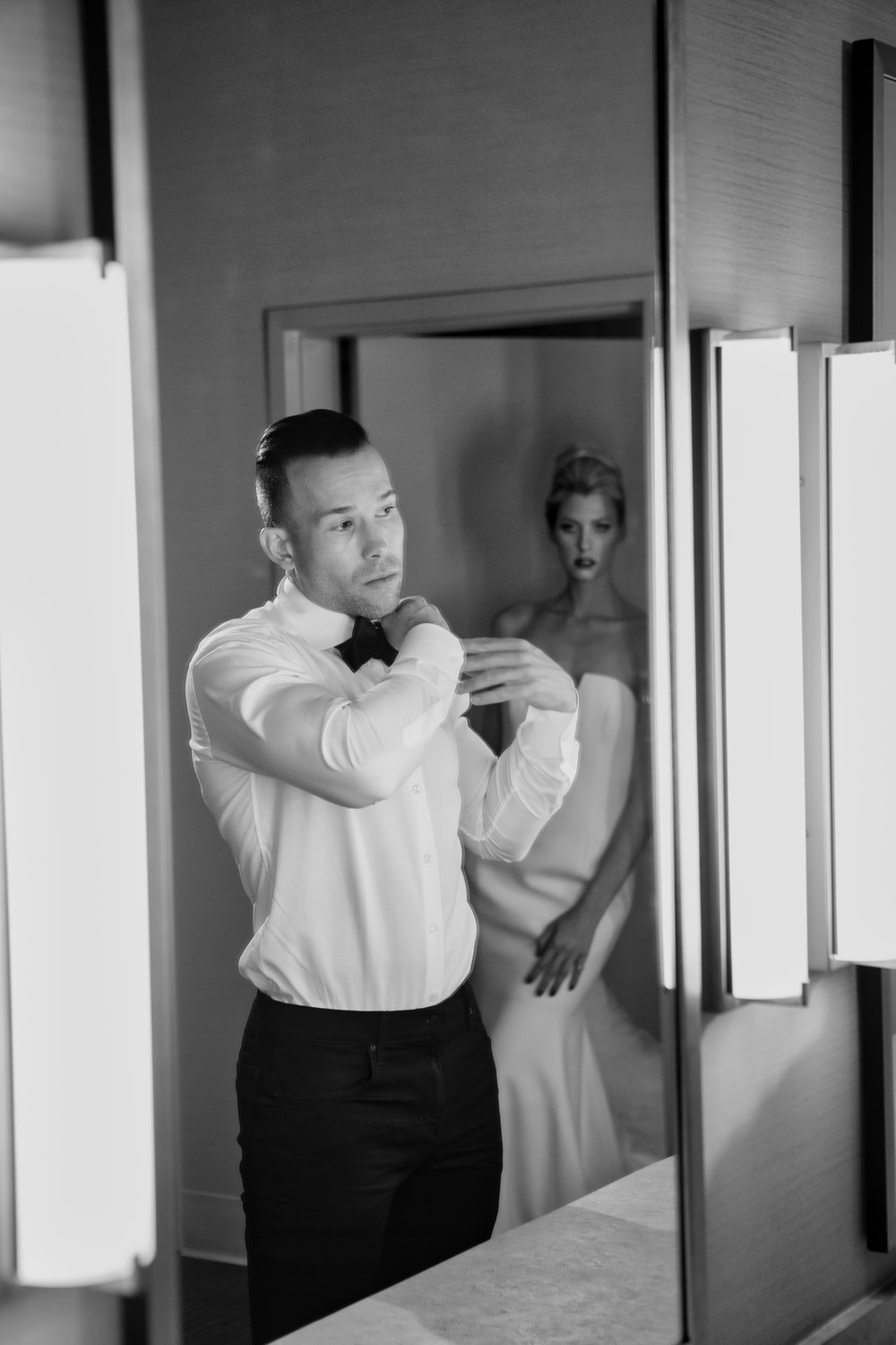Sexy image of bride watching a groom get dressed.  Las Vegas Wedding Planner & Event Designer  Andrea Eppolito Events  · Photography by  Adam Frazier Photo  · Video by  M Place Productions  · Floral & Decor by  DBD Las Vegas  · Venue  ARIA Primrose Ballroom  · Cigar Band by  Royal Cigar Company  and  Jason of Beverly Hills  · Beauty by  Glammed Up Las Vegas  · Dress by  Vera Wang  · Salon  Couture Bride Las Vegas  · Shoes  Bella Belle Shoes  · Bride  Katrina May Armenta  · Groom  Lucas Cuevas