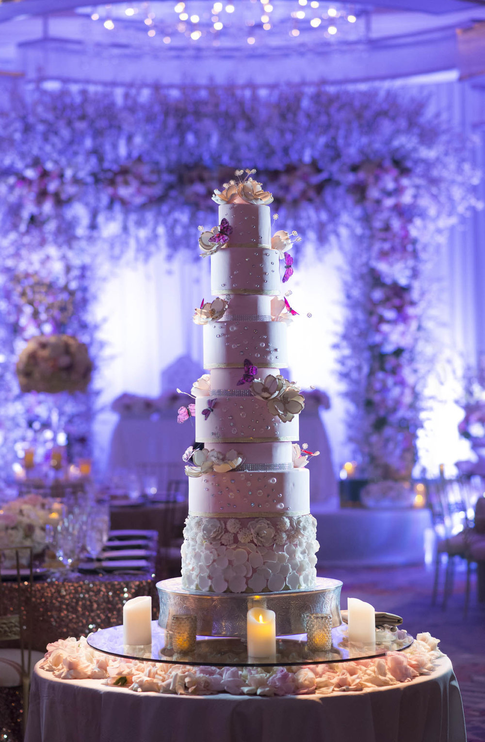 9 tiered wedding cake covered in petals and accented with silk butterflies. Las Vegas Wedding Planner Andrea Eppolito. Photo by AltF.