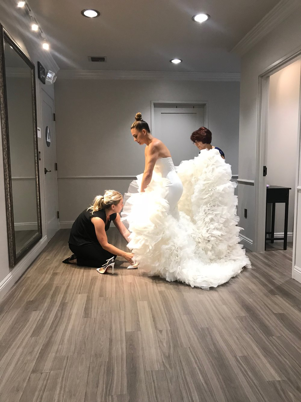 Las Vegas Wedding Planner shares a behind the scenes image of a bride being fit for her wedding dress.