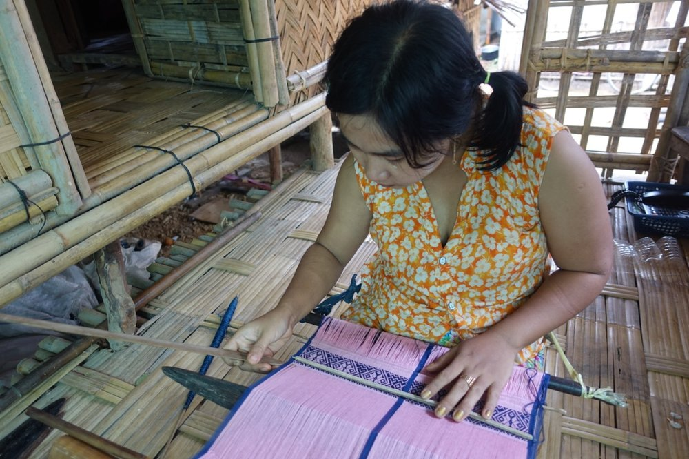 Pin Ei Nwe, is one of the busiest women in Myothit!  She is the mother of 3 young children and her family has a community rice grinding business.  Pin also runs a thread shop out of her home were she sells to all the weavers of Myothit, she also teaches weaving to people who want to learn, and has been designing a line of shoulder bags for Mro society which are super popular! And she has now taken on the supervisor role for all the weavers in the area.