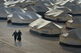 Two women walk in the Za'atari refugee camp located near Mafraq, Jordan. The camp opened in July 2012 to assist some of the more than 200,000 Syrians who have crossed into Jordan to escape an escalating civil war inside their own country. Photo Credit: ACT Alliance/Paul Jeffrey