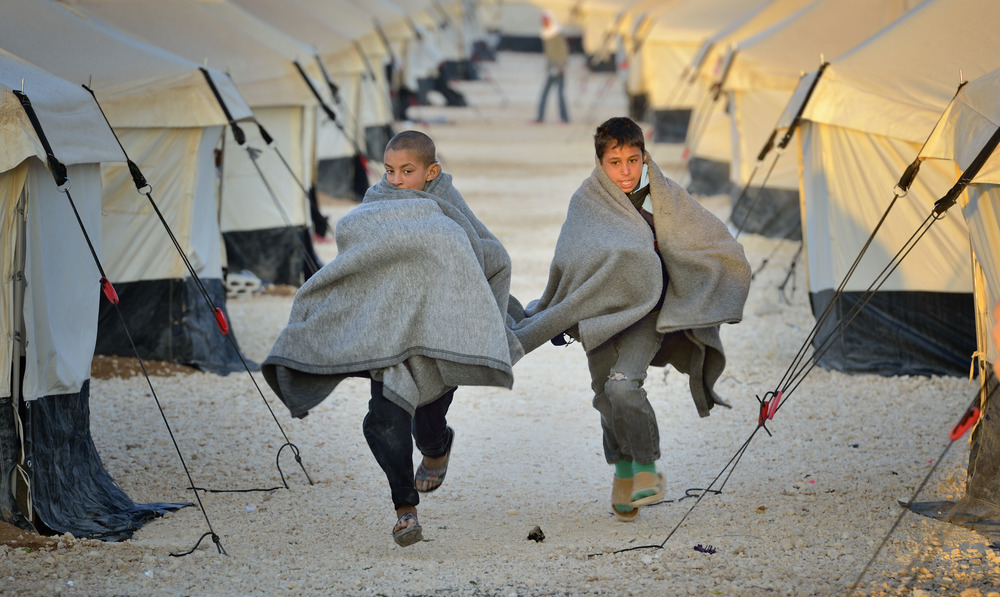 Early in the morning, boys run amid the tents in the Zaatari Refugee Camp, located near Mafraq, Jordan. Opened in July 2012, the camp holds upwards of 20,000 refugees from the civil war inside Syria, but its numbers are growing. Week of Compassion is active in the camp through our partners, providing essential items and services. Photo: Paul Jeffrey