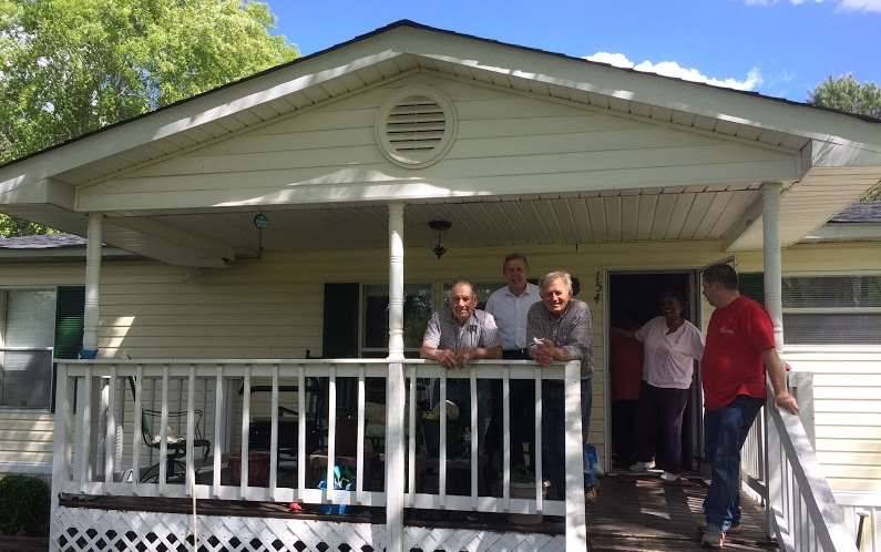 Volunteer crew takes a moment to relax with homeowner, Angela Scott