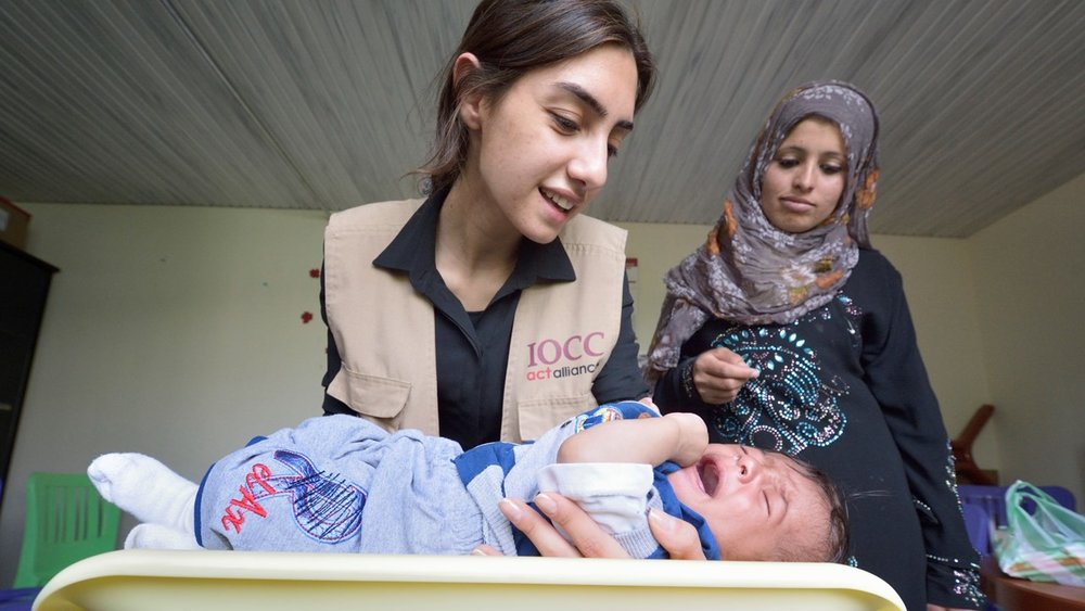 Maha Haidar, a health and nutrition specialist with IOCC weighs five-month old Yasser as his mother Maryam Ismael looks on in the community health center in Kab Elias, a town in Lebanon's Bekaa Valley filled with Syrian refugees. Photo: Paul Jeffrey/ACT Alliance