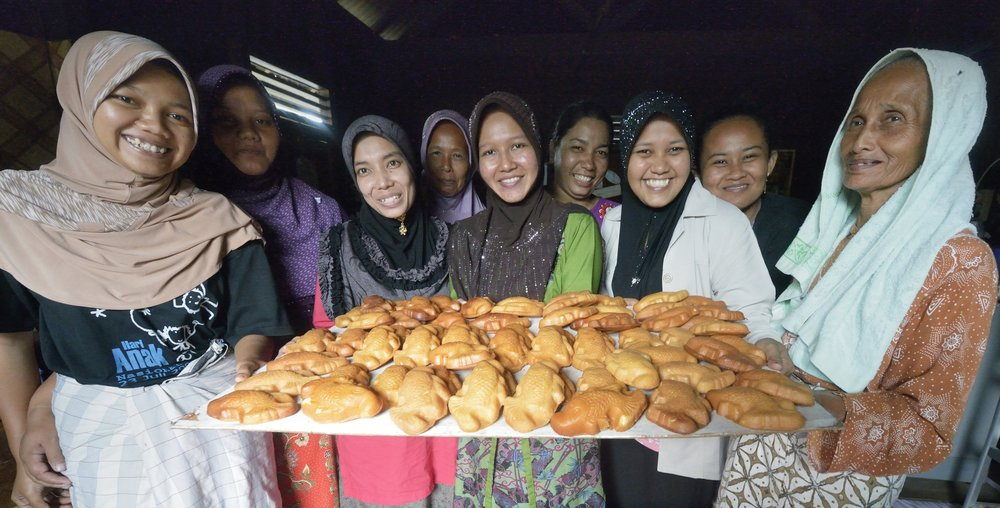 Women in Banda Aceh, on Indonesia's Sumatra Island, who lost their houses and belongings in the 2004 tsunami. The government provided them with a new house. Church World Service, a member of the ACT Alliance, helped the women form a cooperative and loaned them the money they needed to purchase new equipment and ingredients to restart their businesses, including baking pastries like they display here. The women repaid their loans to a revolving fund that they jointly manage. Photo: Paul Jeffrey/ACT Alliance