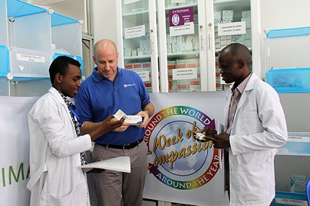 Luke King, IMA's Country Director in Tanzania, center, looks at chemotherapy drugs purchased with funding from Week of Compassion, with pharmacists at Muhimbili National Hospital in Dar es Salaam, Tanzania.(Jennifer Bentzel/IMA World Health)