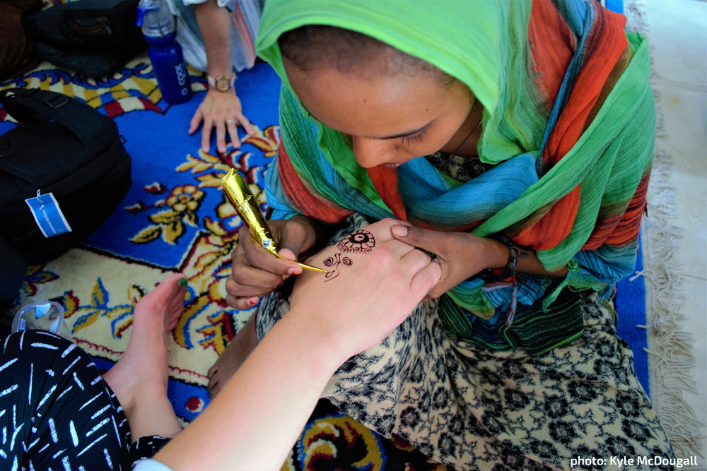 In a gesture of hospitality,  a Somali refugee adorns a  visitor's hand with henna.  [photo: Kyle McDougal]