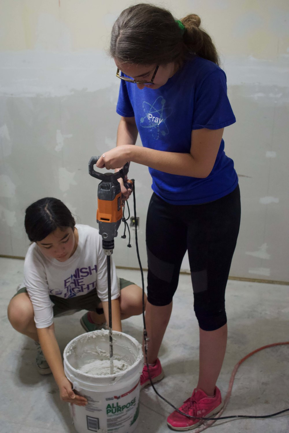 High school volunteers from First Christian Church of North Hollywood prepare wall texture for a home damaged by Harvey.