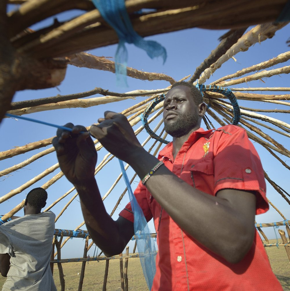 Photo credit: Paul Jeffrey/ACT Alliance   Dau Chol Thuc works on the roof of his new house in Dong Boma, a village in South Sudan after finally returning home after being displaced by rebel soldiers in 2013. Week of Compassion partners are helping the village rebuild.