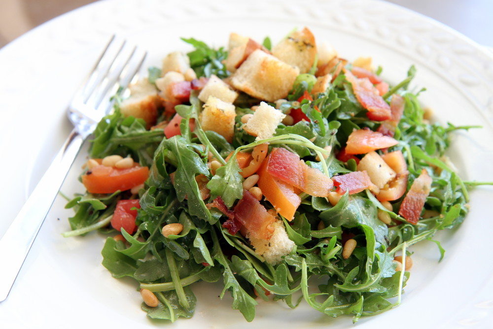 Arugula salad with olive oil, rice wine vinegar, tomatoes, pine nuts, croutons, and bacon