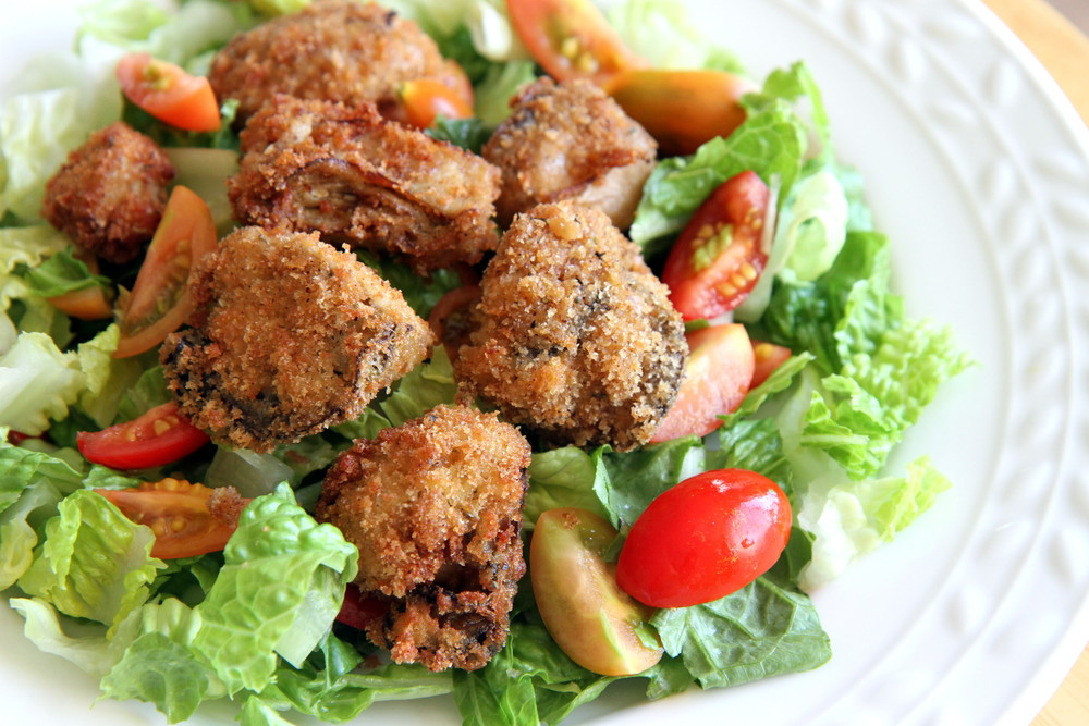 Green salad topped with fried oysters