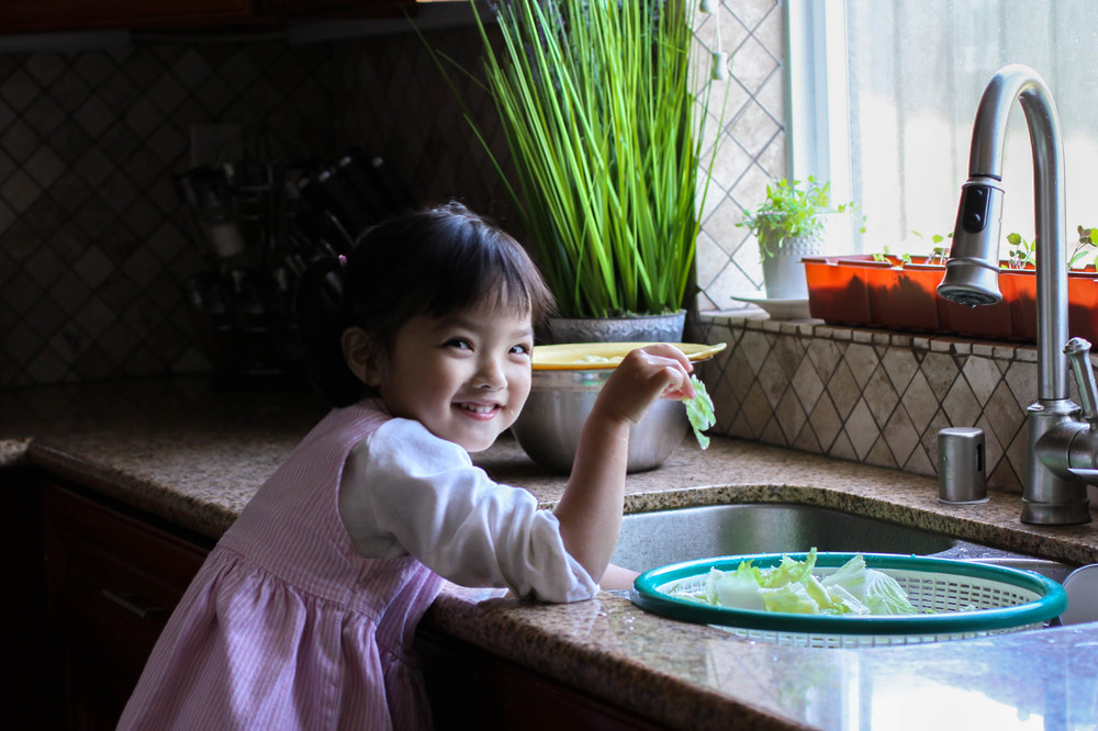Allyson, 3, washes sliced napa cabbage.