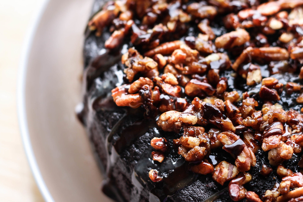 Chocolate cake drizzled with chocolate ganache and topped with candied pecans.