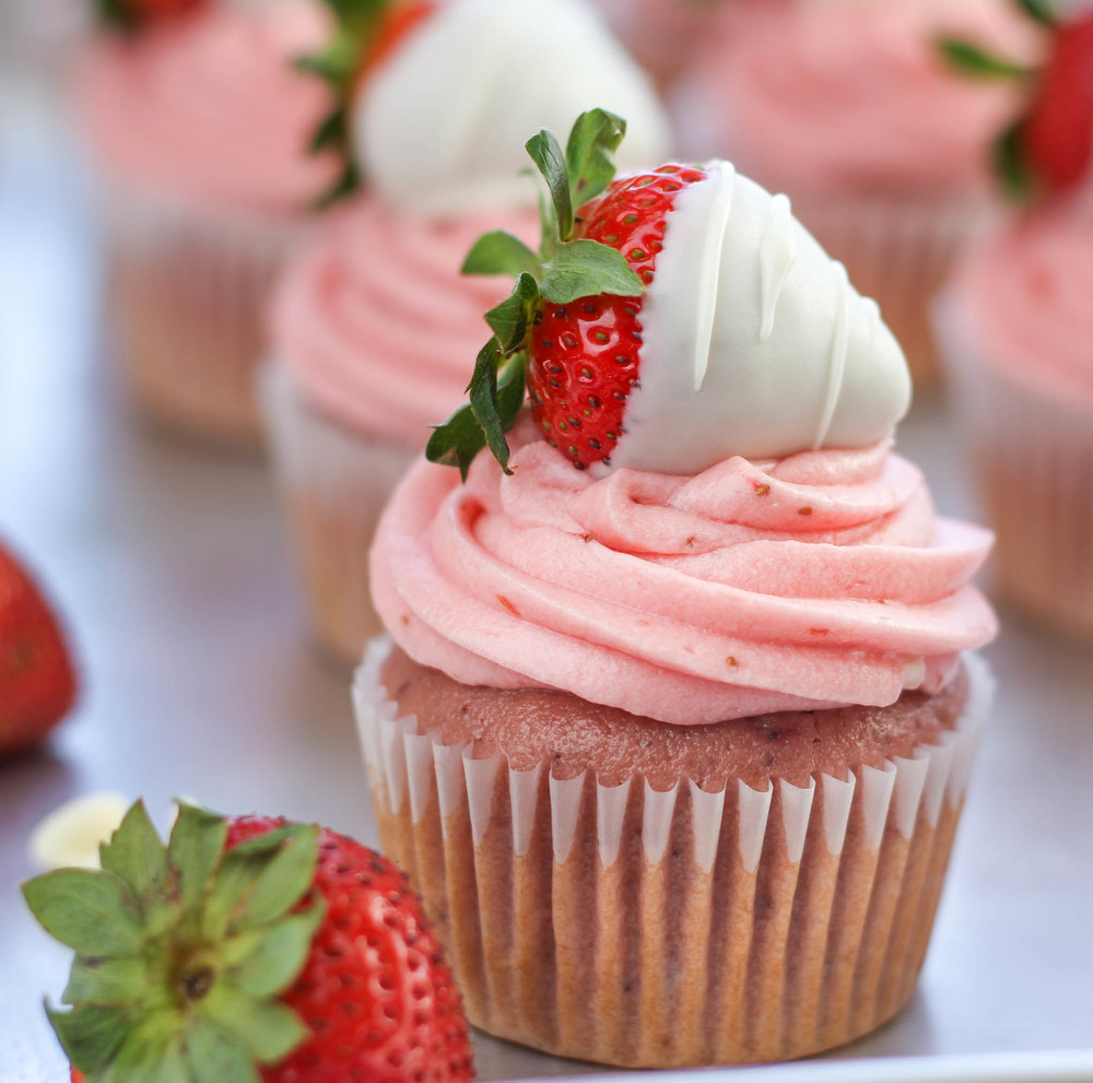 Strawberry cupcakes with strawberry cream cheese frosting, topped with chocolate-covered strawberries