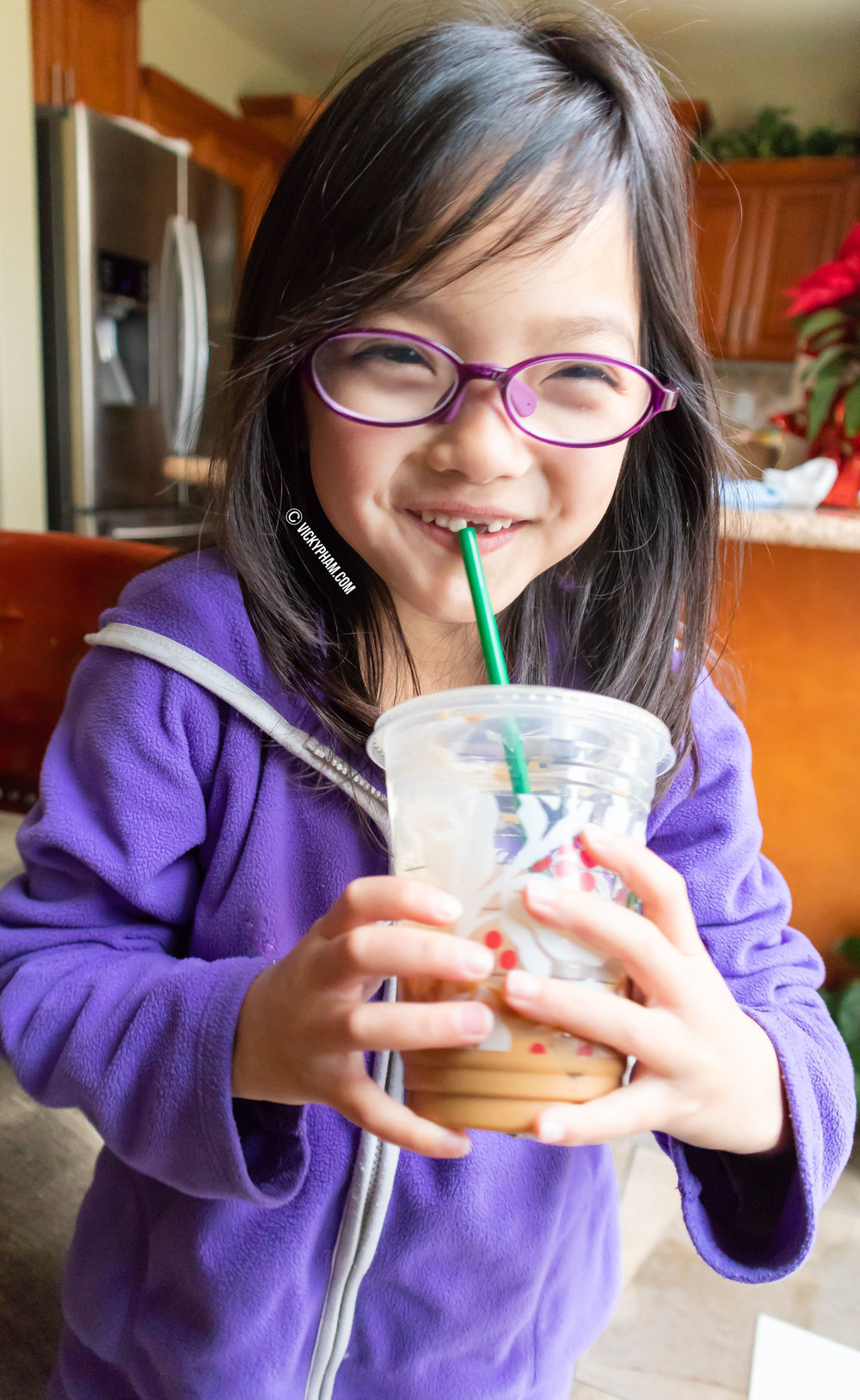 "My beautiful missing-tooth daughter posing with her Starbucks ""Vietnamese Iced Coffee"""