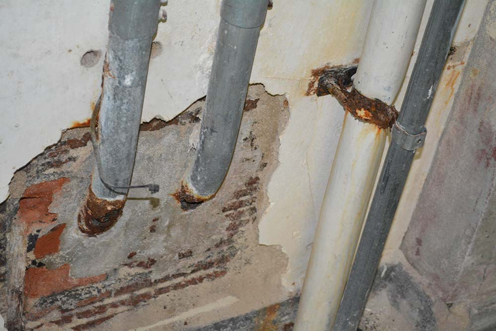 Electrical conduit pipes show corrosion due to water damage