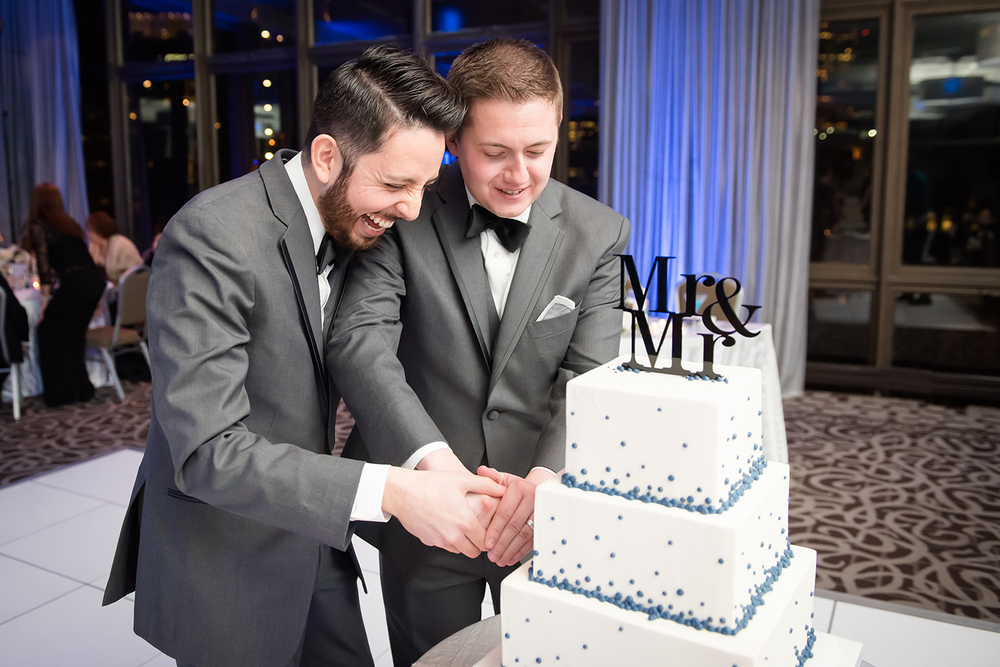 two grooms cutting cake
