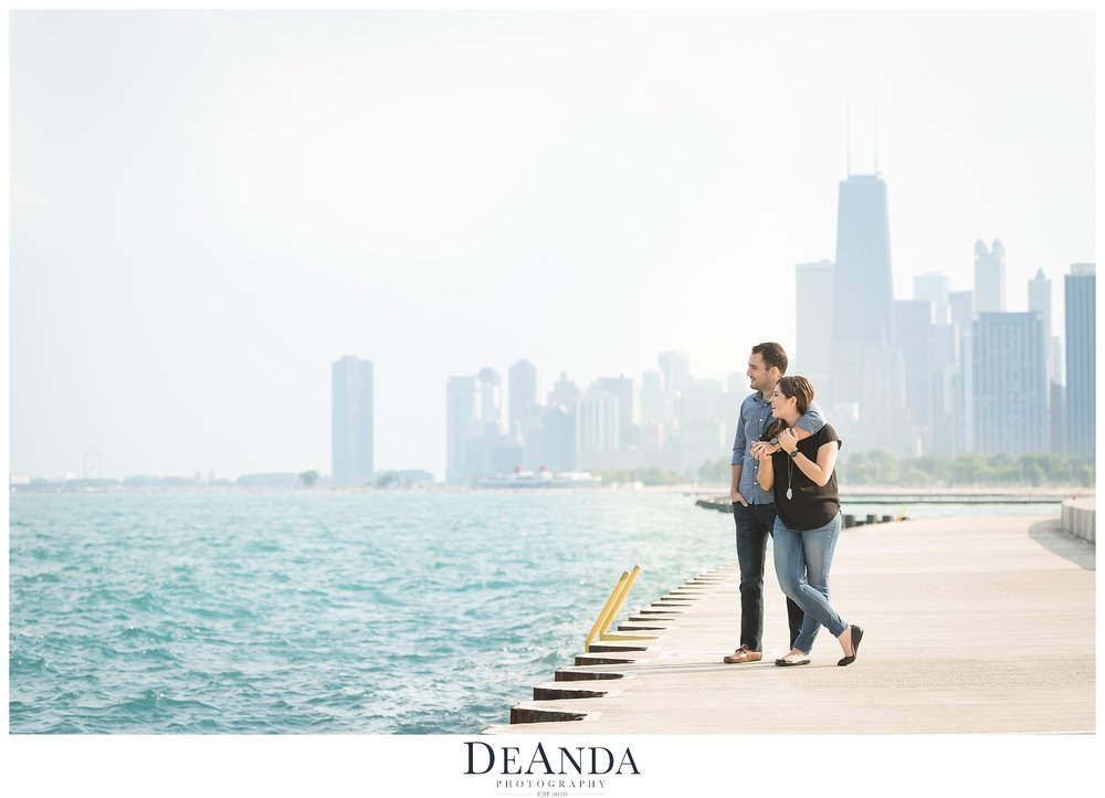 couple on lake front with skyline in the background