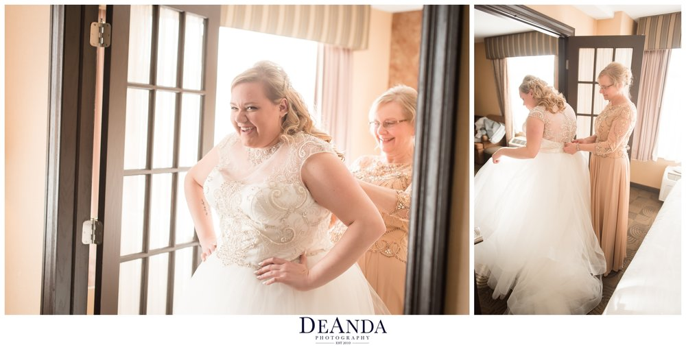 bride getting her dress on with help from mom