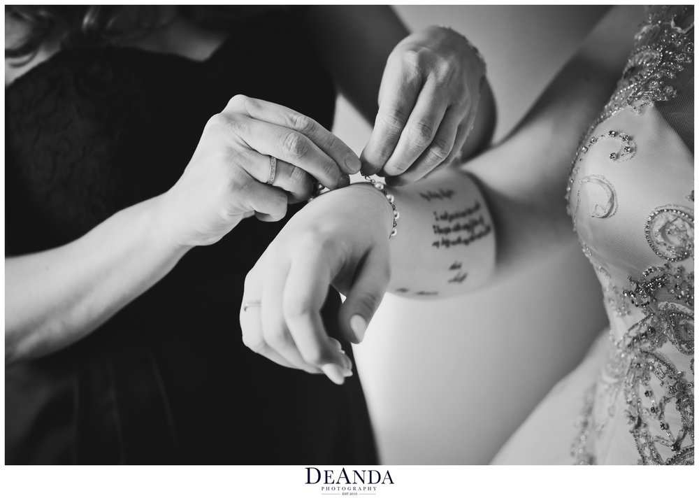 bride having a bracelet put on by a bridesmaid