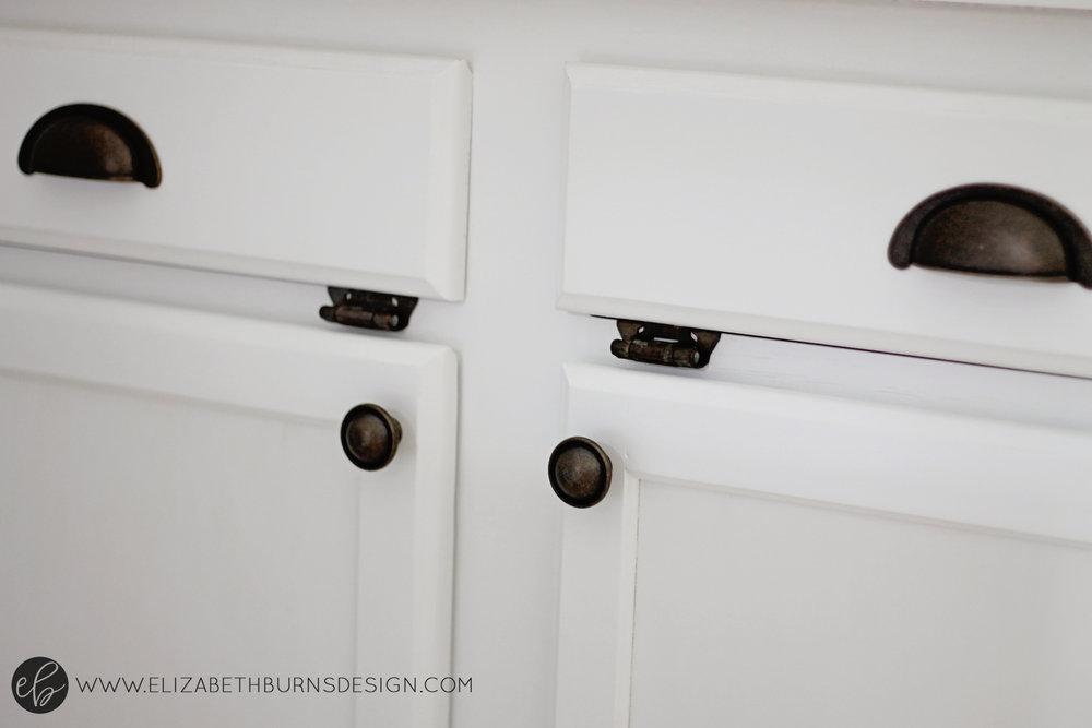 Elizabeth Burns Design | Raleigh Interior Designer - white kitchen cabinets with dark hardware; hardware to match brass hinges on kitchen cabinets