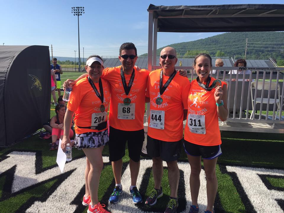 L-R) Randi Hewit (president), Mike Burns (chair, investment committee), John Sirianni (finance officer), and Katie McConville (program assistant) after the 2016 GlassFest 8K presented by the Community Foundation.