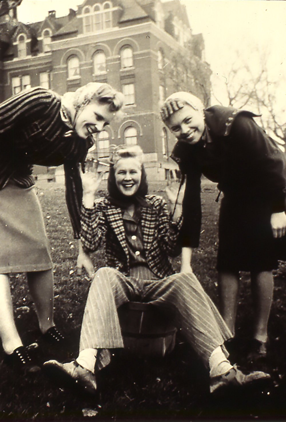 """Swannie"" is in the apple basket as friends pose during campus clean-up day, 1941"