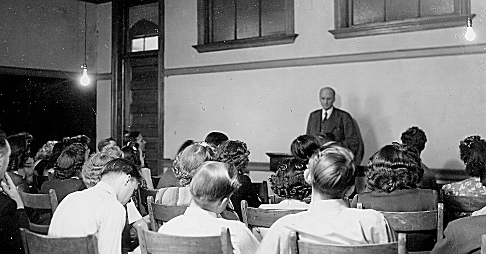 S.L. Klyve stands in front of his class in the 1940s as they practice a written exercise in his Bible course.