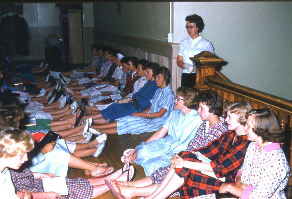 A common sight in evenings around the Castle, night gatherings for communication, prayer, and singing have been an ongoing tradition at Hillcrest. Here, Janet (Monson) Aasby, leads the girls in a chorus during her time as an assistant dean.