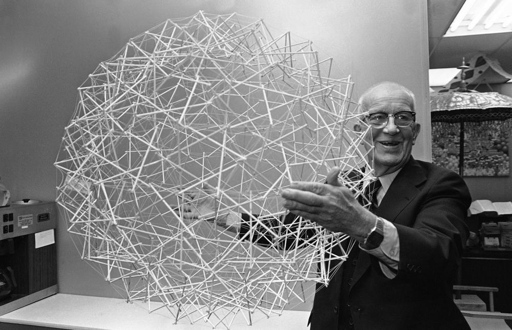 Buckminster Fuller, happily holding a giant tensegrity sphere.