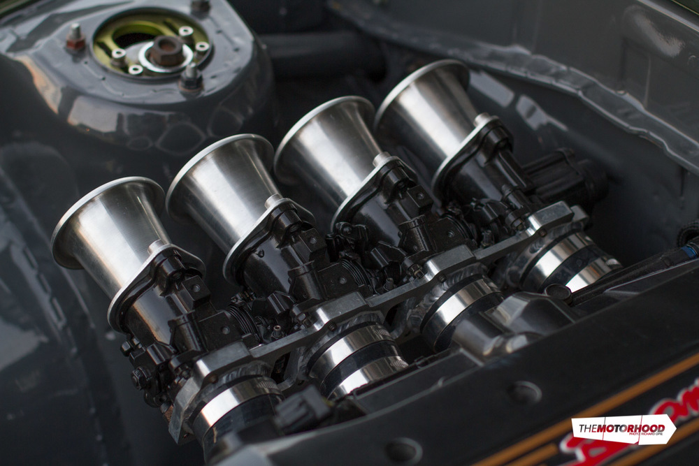 The ITBs use silicone joiners to connect the custom engine and throttle plates. This not only helps isolate the ITBS from heat — a problem the SURFAB AE suffered, with a full-alloy intake that kept cracking — it also allowed them to tune the intake length back-to-back on the dyno to find the optimum power band