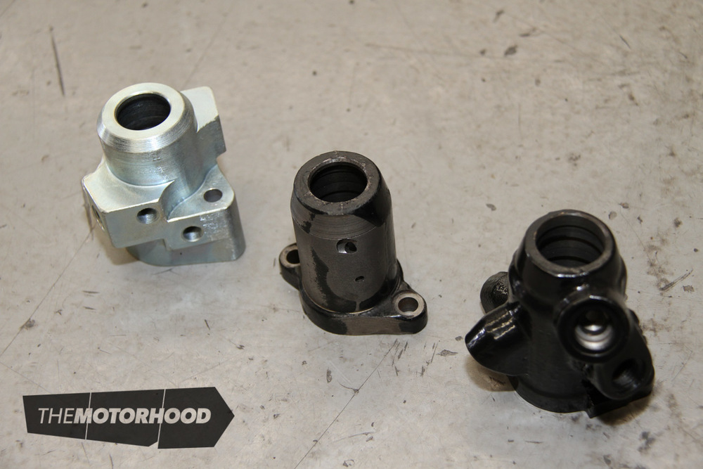 You can see the progress here as the original valve body (right) was first machined down to fit into the narrow space required (centre), before a full custom item was produced (left), shifting the port positions for optimal hose position.