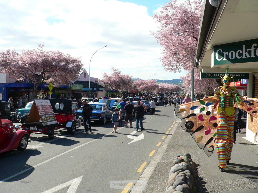 Chadwick Road, cars on display, Cherry Blossoms and the stilt walker dressed up as a giant moth.jpg