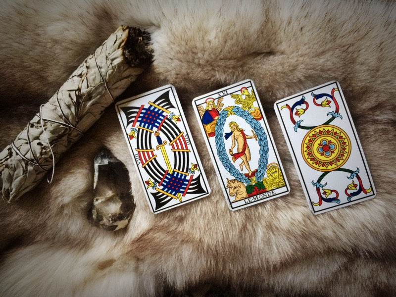 Nine of Swords, The World, and Ace of Pentacles.