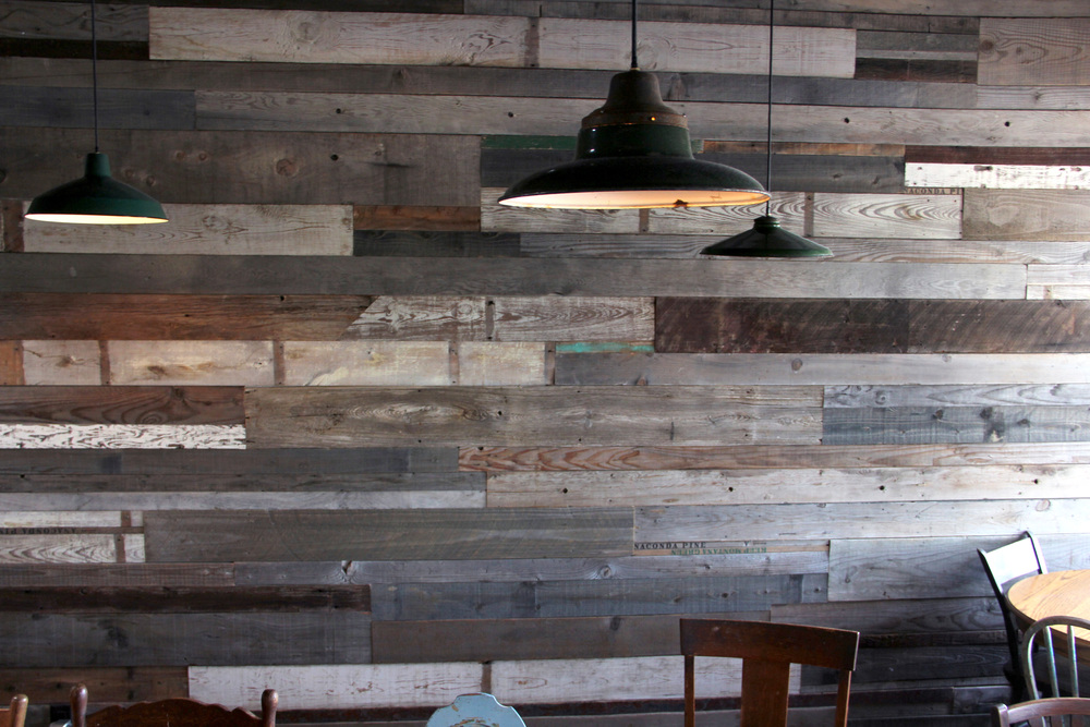 This wood paneled wall is pieced together with wood from New York, Virginia, Tennessee, Arkansas, Oklahoma, Texas, and California. Each piece was rescued from collapsed or abandoned grain mills, barns, rail road stations and dumpsters.