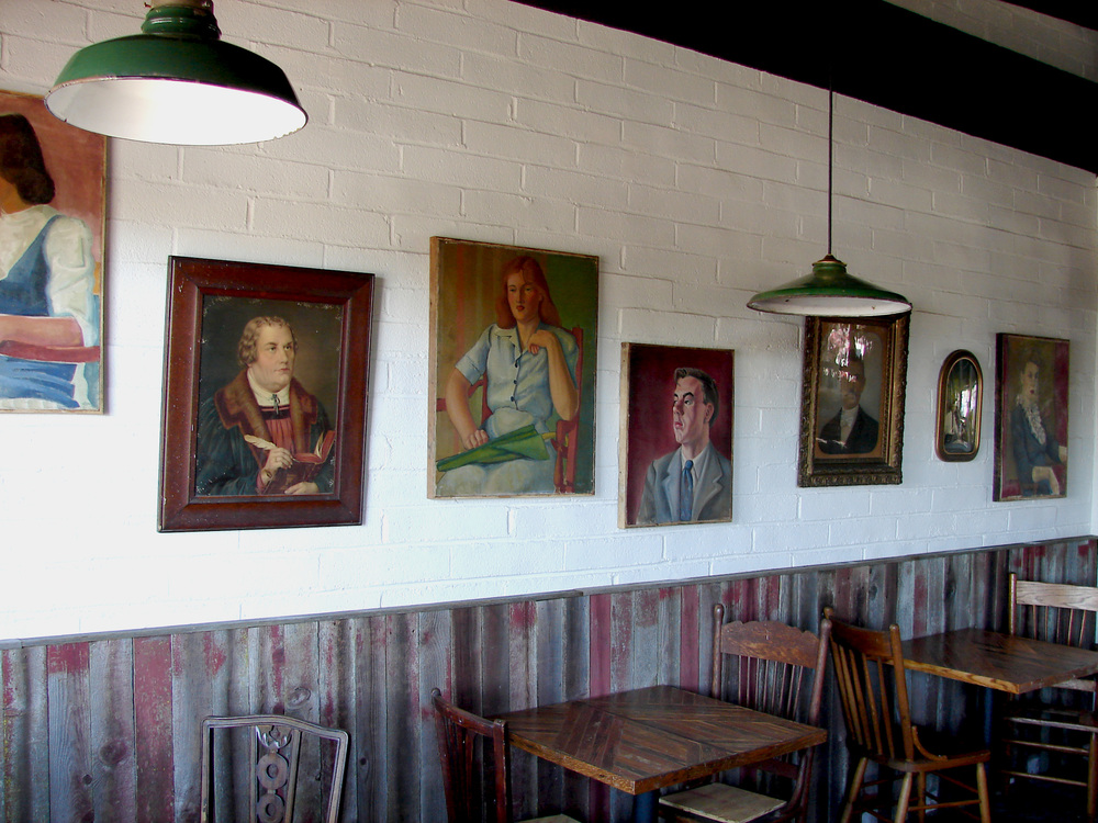 The wood wainscoting is an old redwood fence, once painted red, and faded to silver perfection. The green enamel lights were found in junk stores in Virginia, and the various portraits were collected from many different states. Most of them date to early 40's.