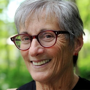 Picture of the incredible activist Gina Glantz founder of Gender Avenger dot com. This is a portrait. She is wearing glasses. Has short dark hair. And a friendly smile.