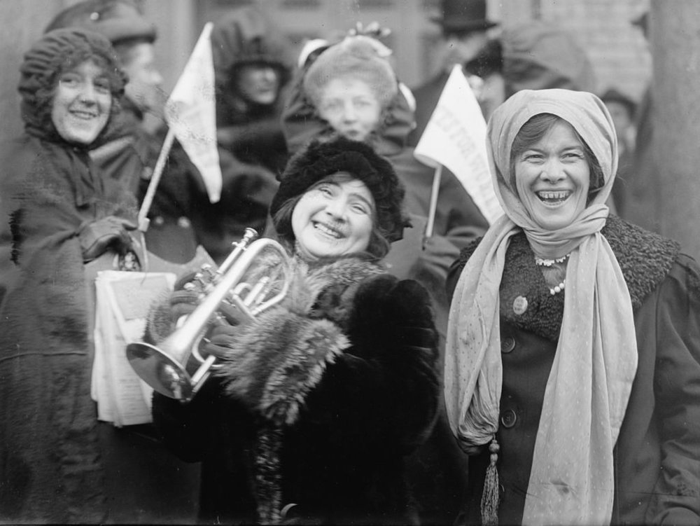 "Women's suffragists demonstrate in February 1913. The triangular pennants read ""VOTES FOR WOMEN""."