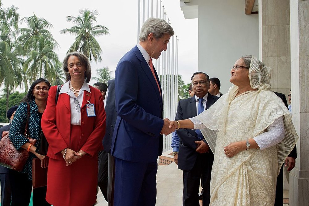 U.S. Secretary of State John Kerry greets Bangladeshi Prime Minister Sheikh Hasina Wazed at the Prime Minister's Office in Dhaka, Bangladesh on August 29, 2016. Photo credit: U.S. Department of State from United States [public domain],  via Wikimedia Commons