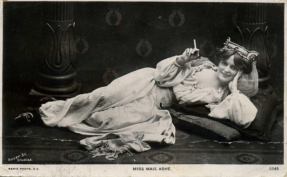 1024px-Miss_Maie_Ashe,_actress,_reclining,_smoking_a_cigarette_(postcard).jpg