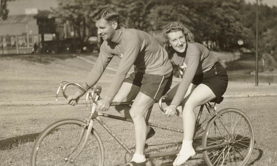 Oppy_(Hubert_Opperman)_and_woman,_possibly_Edna_Sayers,_on_tandem_bicycle,_by_Sam_Hood_(5864590841).jpg