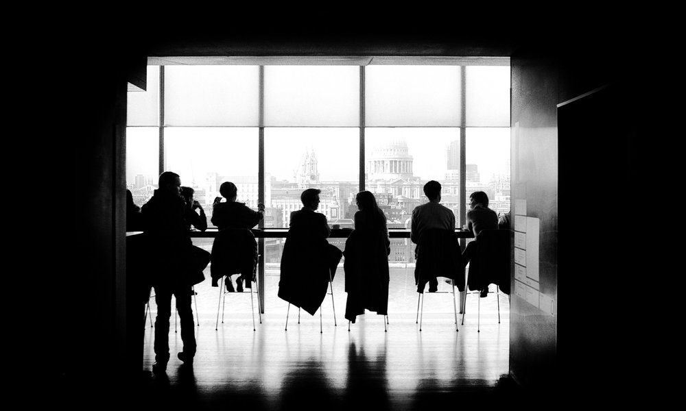 a photo of a silhouette of several people sitting around a table