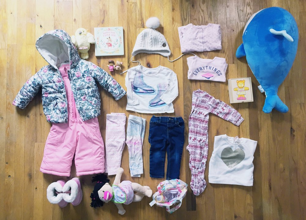 Clock-wise From Top Centre:  White Winter Hat |  H&M,  White Shirt with Skates on it |  The GAP,  Folded Pink Pyjamas |  Joe Fresh,  'Everything's S'more Fun With You' Folded Pink Shirt |  Carters , Blue Whale |  Christmas gift from Auntie Nicole,  Wodden Teddy Cut Outs |  Melissa & Doug Gift from Grandma & Grandpa,  White Heart Sweater |  Carters,  Red Nordic Pyjamas |  Joe Fresh,  Jeans |  Second hand , Snowflake Pants |  The Gap,  Pink Nordic Pants |  Joe Fresh,  Stella Doll Diaper Bag & Accessories |  Various Gifts from Grandma & Grandpa,  Stella Doll |  Indigo , Winter Boots |  Joe Fresh,  Pink Snow Suit Pants & Coat Set |  Joe Fresh,  Yellow Bird |  Japan - Gift From Auntie Jasmine , 'Baby Roo I Love You' Book |  Indigo  -  Valentines Day Gift from Mama & Dada,  Little People Girl & Teddy |  Gift from Grandma & Grandpa
