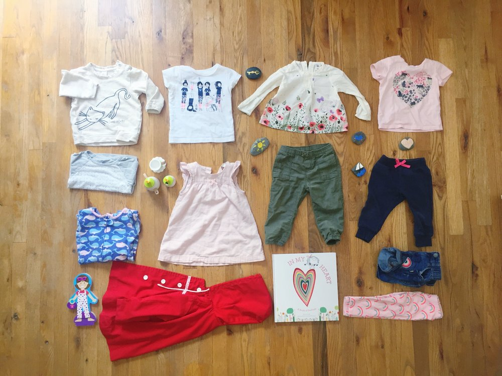 Clockwise from Centre:  Key Rock made by Jasmine Alexander, Light Flower Long Sleeve - Carters from Mimi & Yeye, Pink Cat Heart T-Shirt - Joe Fresh, Heart & Sailboat Rocks painted by Jasmine Alexander, Blue Bird Rock painted by Amy Grace, Blue Jogging Pants - Carters, Jean Shorts - Carters, Rainbow pants - Children's Place, In My Heart: A Book of Feelings - by Jo Witeck & Christine Roussey - Indigo - , Red Hooded jacket - From my childhood, Green Pants - Carters, Pink Dress - H&M, Magnetic Doll - Melissa & Doug from Grandma & Grandpa, Whale Panamas - Carters, Tea Set - Hape From Mimi & Yeye , Grey and White Baseball T - Carters, Caterday Sweater - Joe Fresh, Yoga T-Shirt - Carters